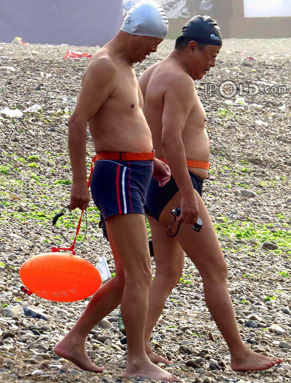 Swimming old men in boxer pants at the sea