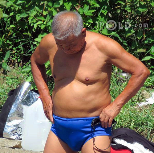 Swimming old daddy in blue underwear standing by the lake