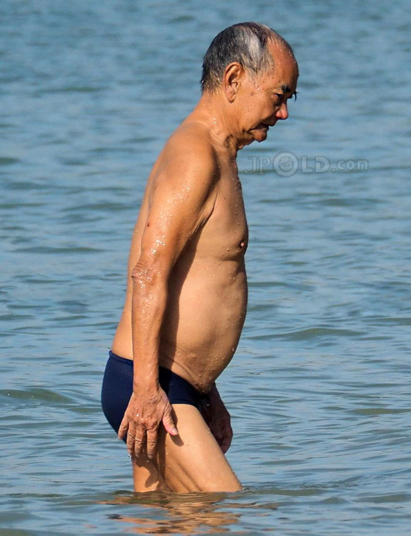 Skinny swim old man in purple swimsuit pants at the sea