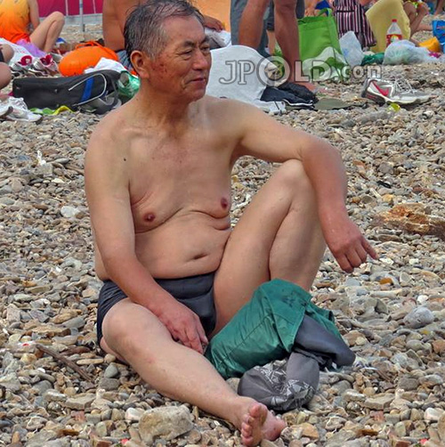 Old man in grey pants sitting on the beach
