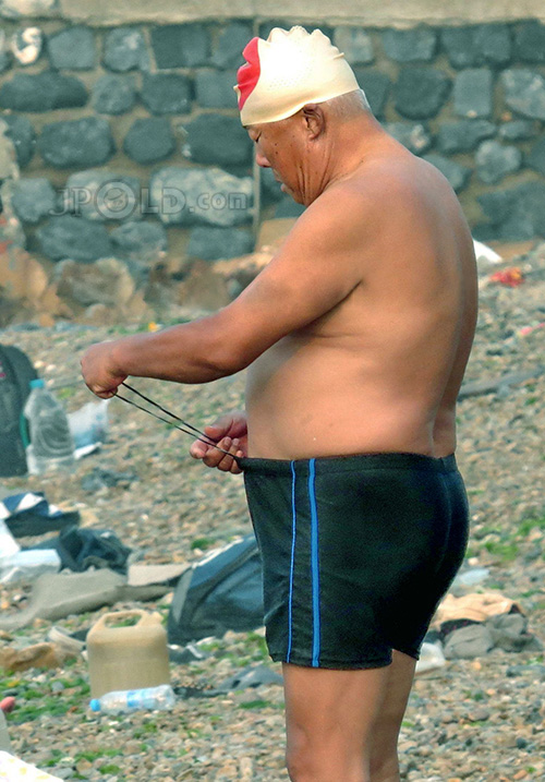 Fat old man in black boxer pants goes swimming