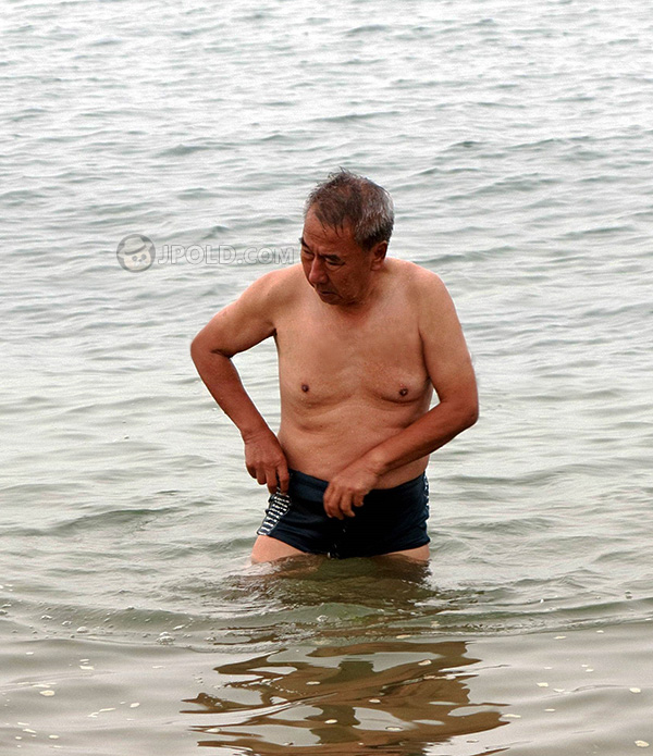 Old man in purple boxer pants swimming in the river