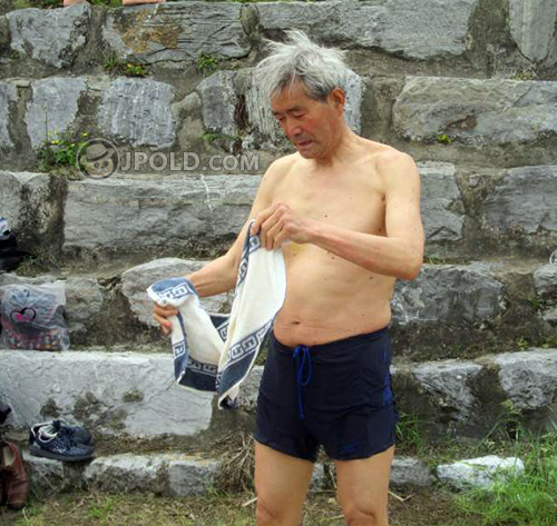 White hair grandpa in purple short-pants by the lake