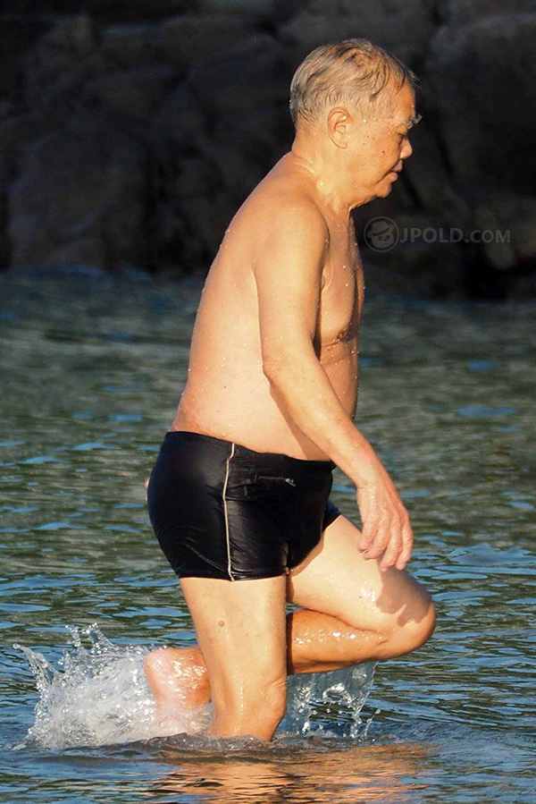 Swimming bald old man in a black underwear in the front of