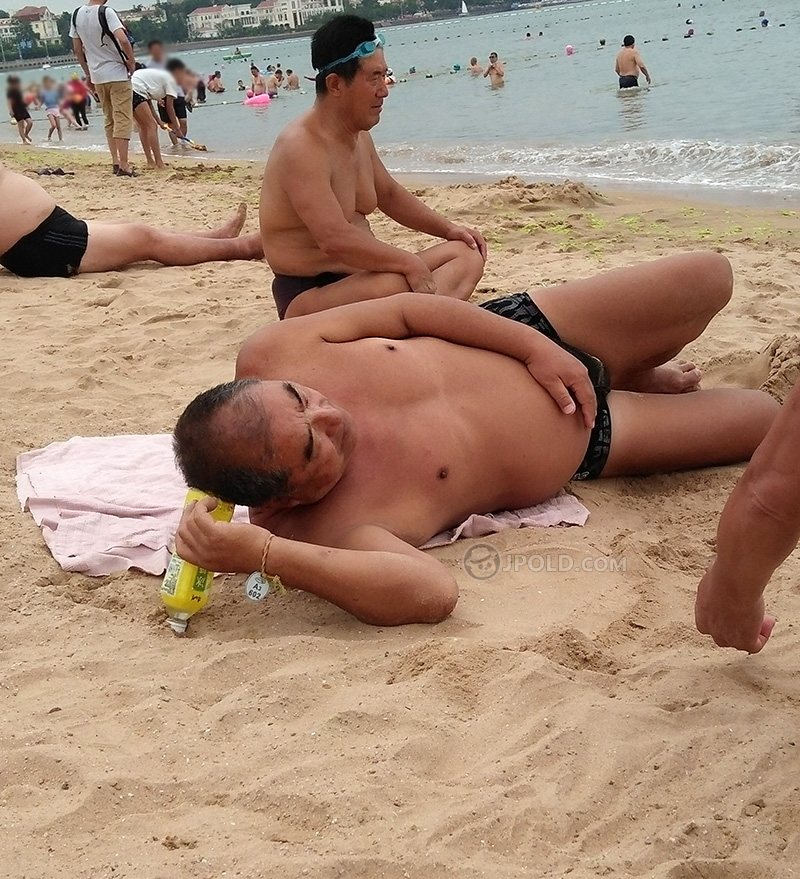Old daddy in a black underwear was lying on the beach