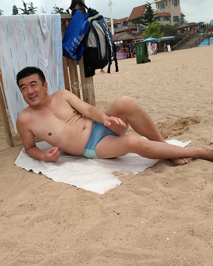 Swimming daddy in a blue underwear was lying on the beach