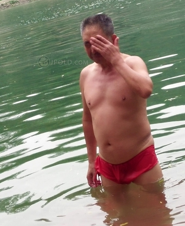Swimming old daddy in a red underwear in the lake