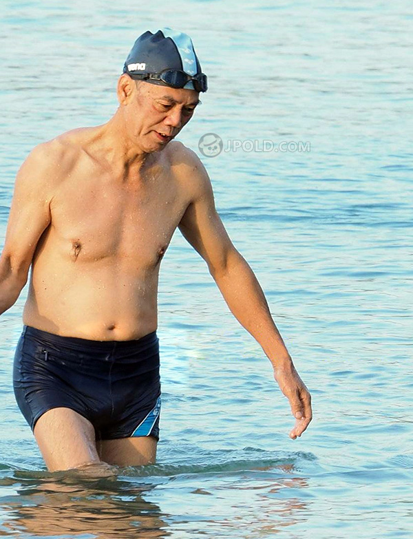 Old man in black swimsuits out of water