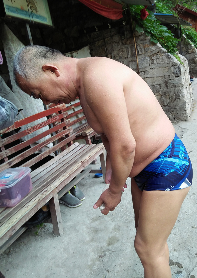 Charming swimming grandpa in a blue underwear by the lake