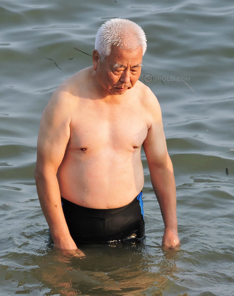Charming white hair swimming grandpa in a black underwear at the sea