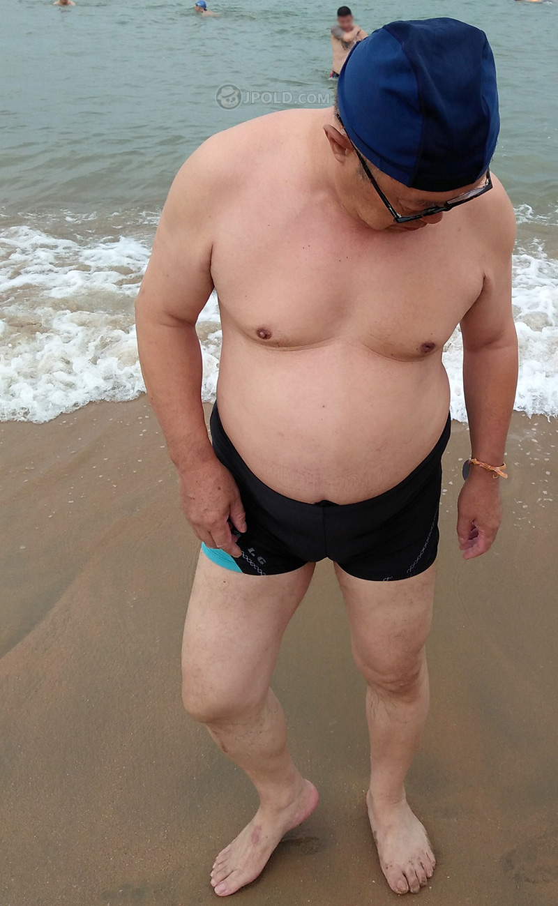 Handsome glasses grandpa in black boxer pants at the sea