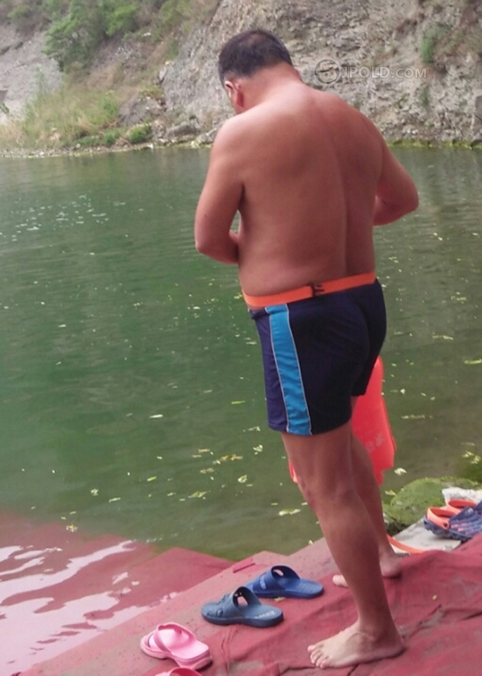 Swimming old daddy in a black pants ready by the lake