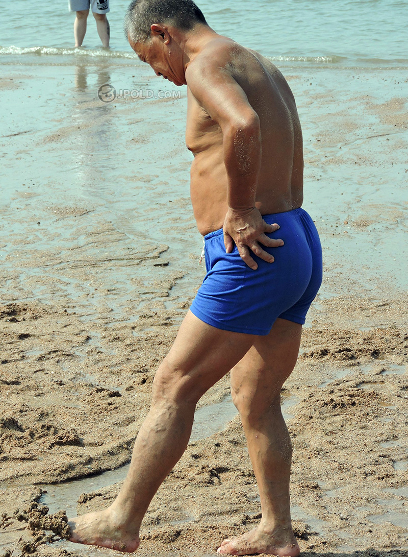 Old man in a blue boxer pants on the beach