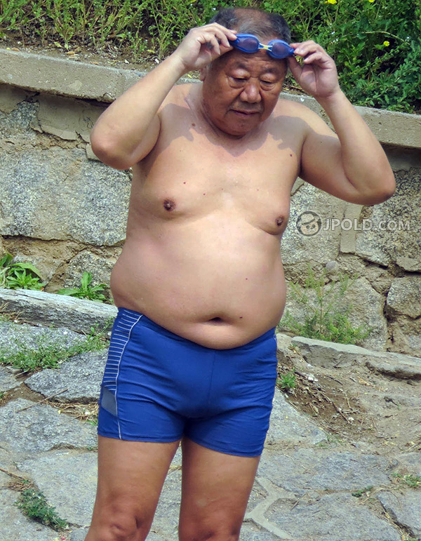 Fat swimming old man in a blue pants by the lake
