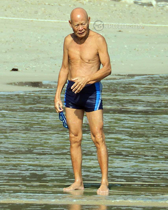 Skinny swim old man in a black boxer pants was running at the sea