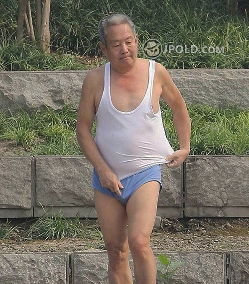 Old man in a blue underwear by the lake