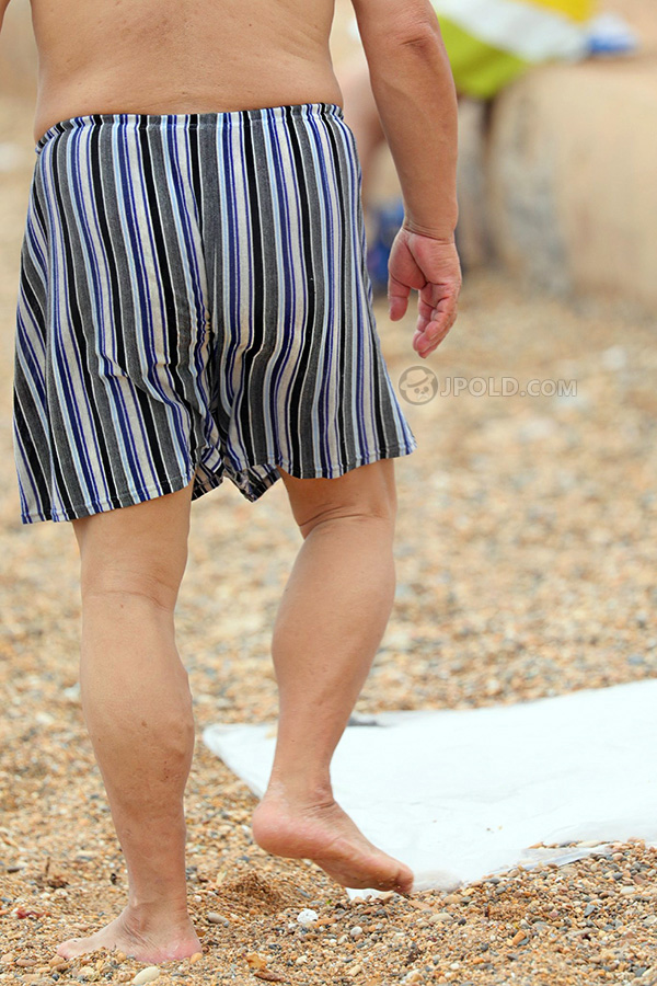 Old man in a stripe pants on the beach