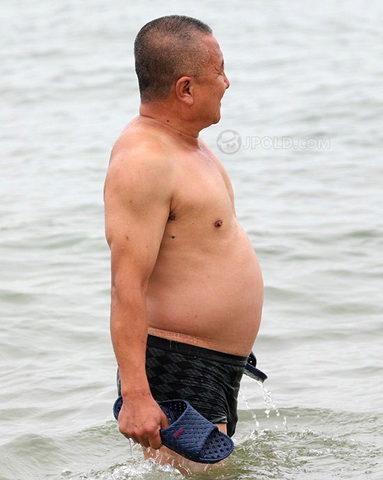 Old daddy in a black swimsuit pants at the sea