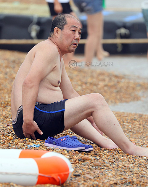 Some swimming old men in a underwear rest on the beach