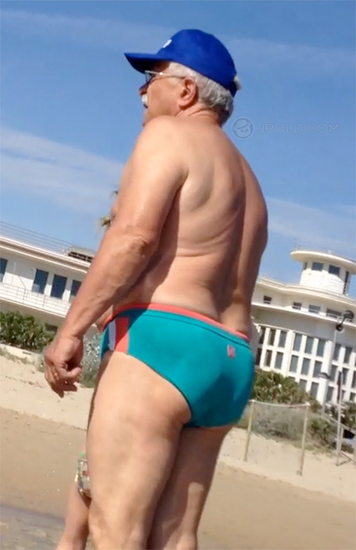 Old man in a light blue brief on the beach