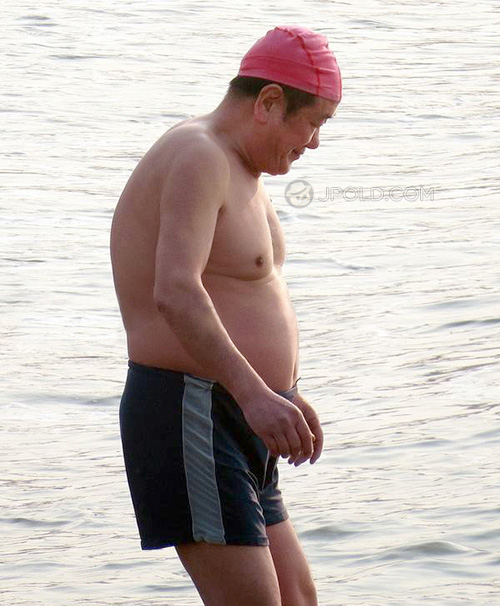 Fat swim old man in a black underwear by the river