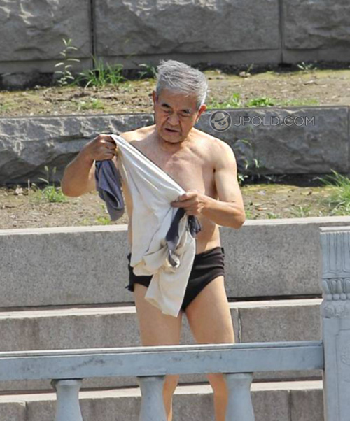 Swim white hair old man in a black underwear by the river