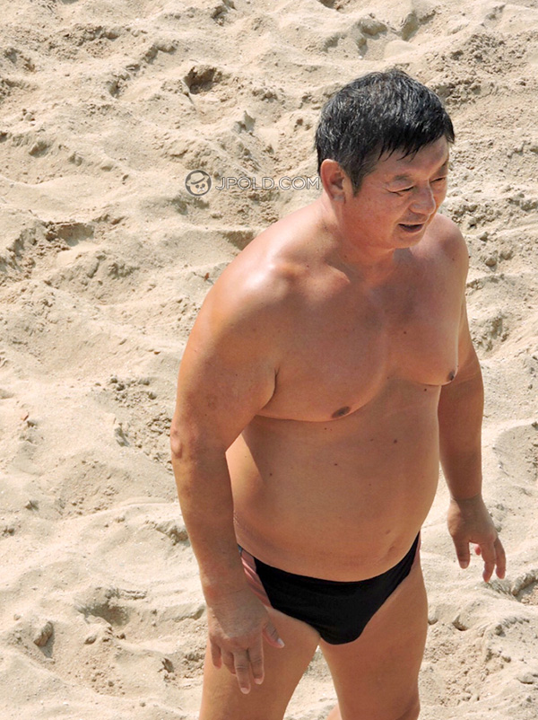 Strong daddy in a black underwear on the beach