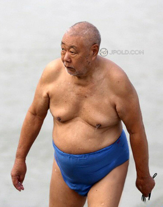 Fat swimming old man in a blue underwear by the lake