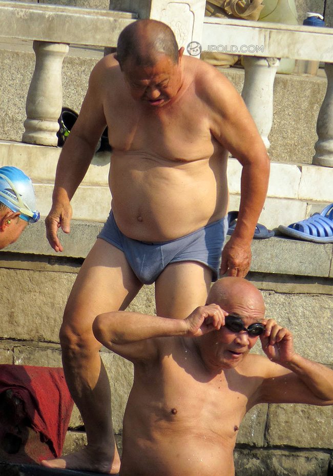 Fat old man in a blue underwear went swimming