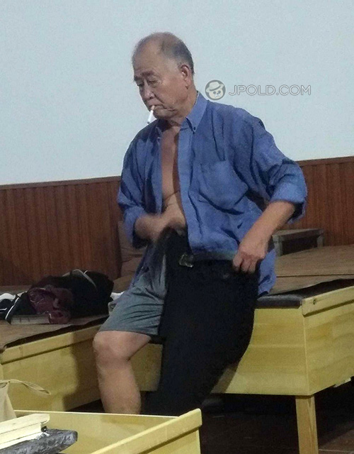 Blue shirt old man in the public rest-room