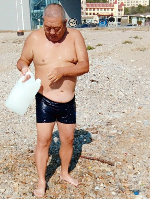 Old daddy in a purple boxer underwear on the beach