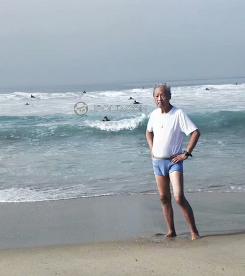 Thin old man in a white T-shirt and a blue underwear on the beach