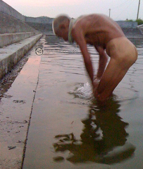 Some thin swimming old man stood by the pond