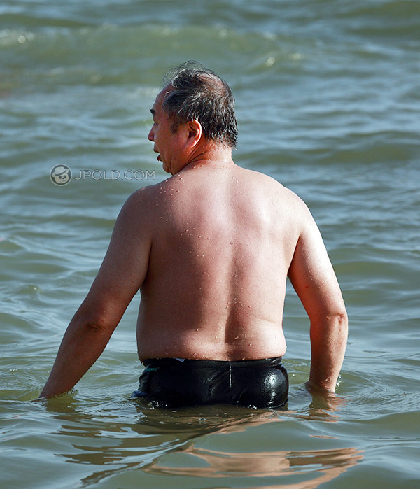 Handsome old man in a black underwear at the sea