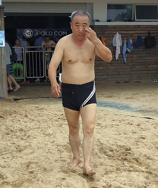 Old daddy in a black boxer underwear on the beach