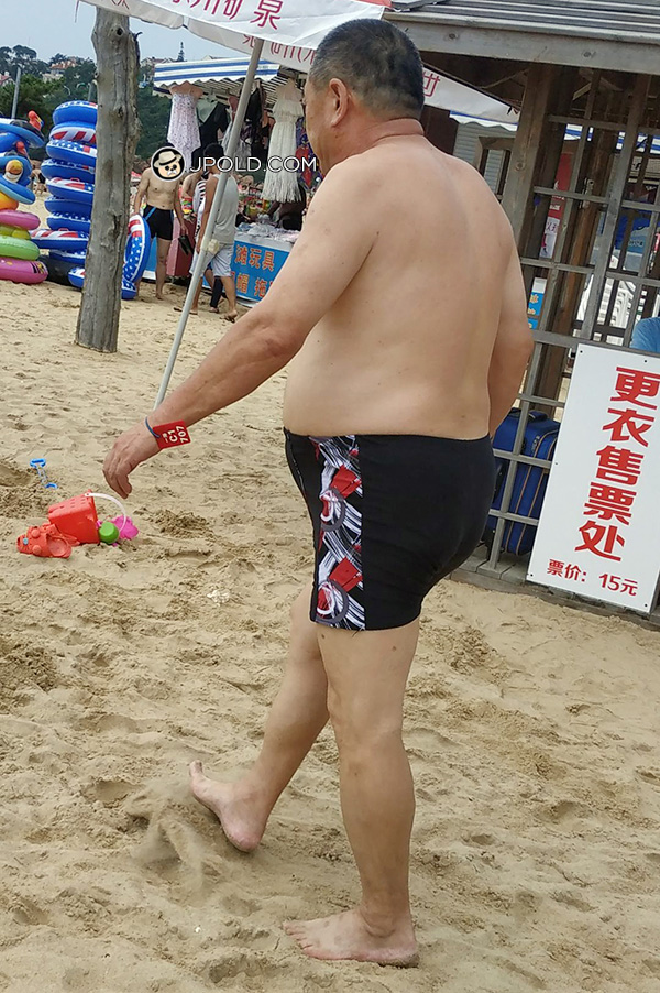 Old daddy in a brown boxer underwear on the beach