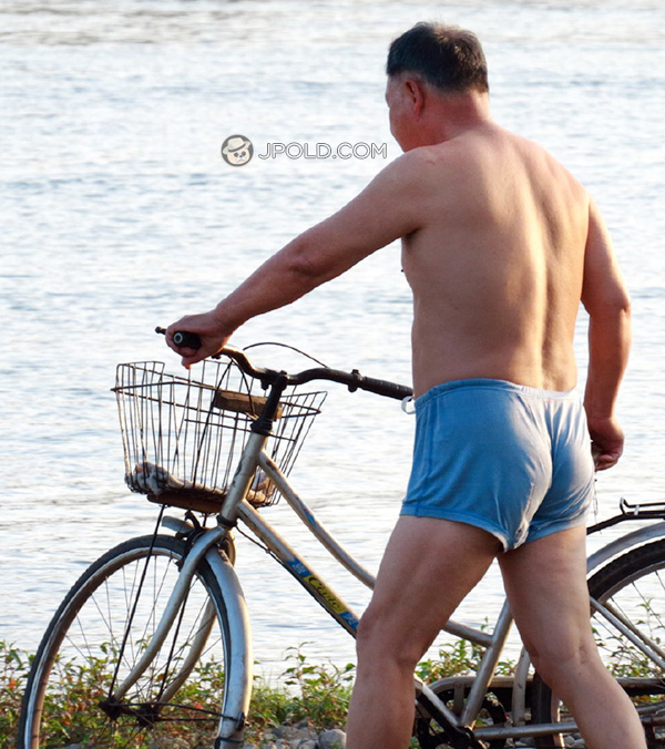 Swimming old daddy in a blue underwear by bike