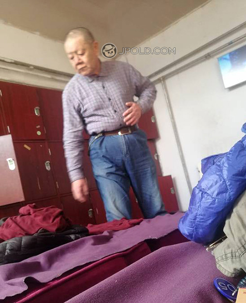 Old man put on his clothes in the public rest-room