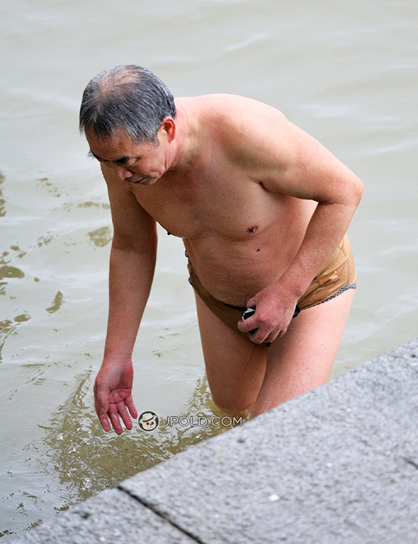 Swim old man in a underwear out of river