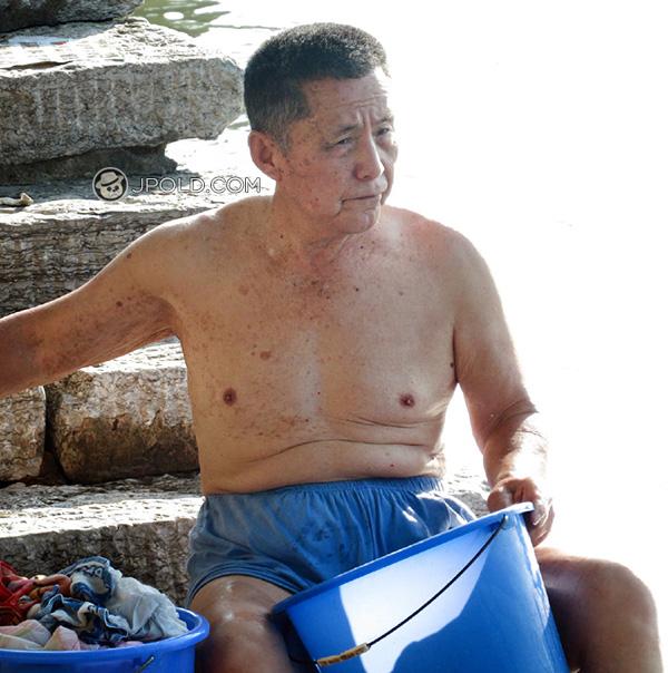 Old daddy in blue underwear was washing shoes by the river