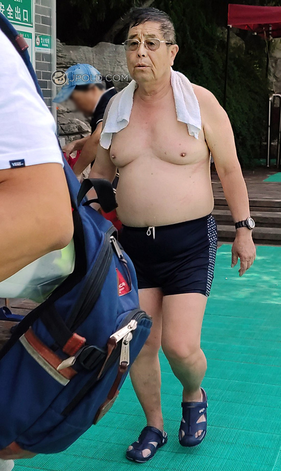 Glasses old man in a brown boxer underwear went swimming