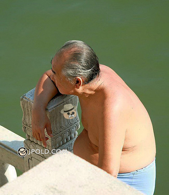 Swimming old man in a blue underwear sat by the river
